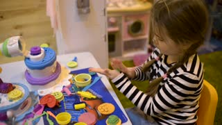 Girl kid playing with plasticine colorful