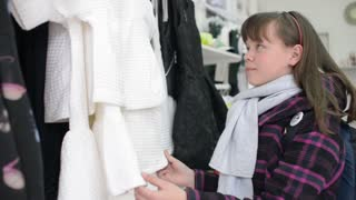 Girl schoolgirl in a coat with a backpack in trendy clothing store shopping
