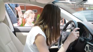 Girl sitting behind the wheel of a Lexus at the auto show and car market