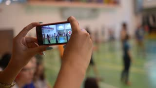 Girl take video via Mobile Sell Phone - students play Volleyball in School Gym