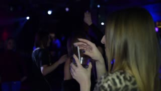 Girl with a Glass of Cocktail drinks and dancing at a Nightclub