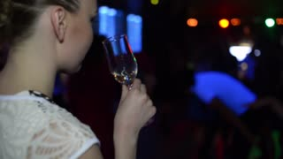 Girl with a Glass of Wine drinks and dancing at a Nightclub