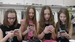 Girls Children with their Smartphones and mobile phone shating in clothes store