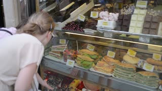 Girls choose snacks in the window in the cafe in Venice