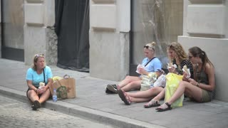 Girls Tourists Eat Street Food Sitting in the Square in a Crowded Place - Krakow