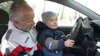 Grandfather teaches his grandson a little drive - spinning wheel