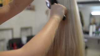 Hairdresser combing hair blond wig