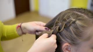 Hairdresser plaiting braids for girls brunette
