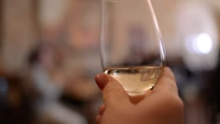 Hand Shaking A Glass Half-Filled With White Wine