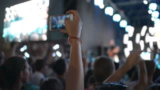 Hands Hold Mobile Camera With Digital Display Among People During Rock Concert