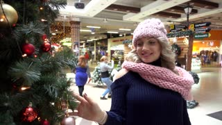 Happy Blonde Woman on Christmas Fair under Tree Having fun
