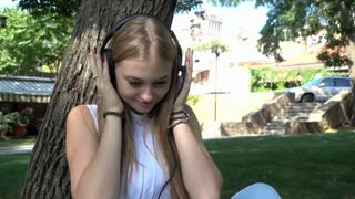 Happy cute Girl listening to Music through Headphones in the Park