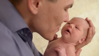Happy father holds his newborn naked little baby girl in the hands