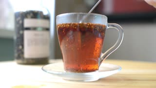 Herbal tea in a glass with a spoon stir