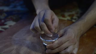 hookah smoking - a guy with a needle pierces the foil