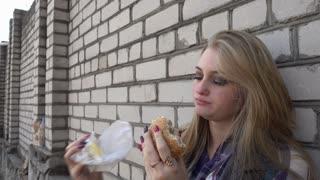 Hungry Blonde Girl eating a Sandwich Hamburger at a brick Wall