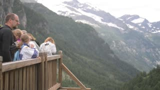 In the Alps, tourists admire the mountain peaks