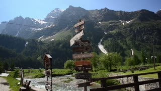 Italian Alps. Signpost. Bridge across the mountain river, the green valley and snow-capped peaks of Alps