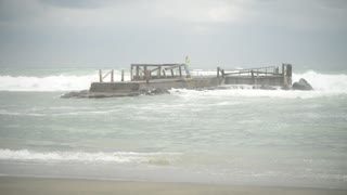 Italy coast Tyrrhenian sea in stormy weather - Waves fall on the old wooden pier