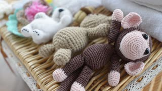 knitted baby animal toys are in a wicker basket