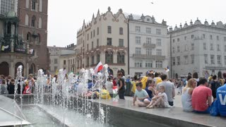 Krakow Market Square fountaine, tourists walk and sitting having fun