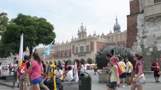 Krakow Market Square, pedestrians, tourists, walk and sitting having fun