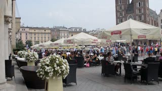 Krakow Market Square, people relaxing sitting at cafe tables drinking coffee