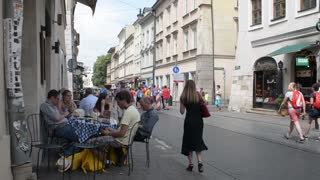 Krakow Market Square, people relaxing sitting at street cafe table drinking beer