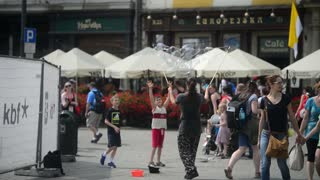 Krakow Market Square, tourists, walk and having fun with  bubbles