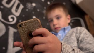 Little Boy with Smart Phone in Hands browse network