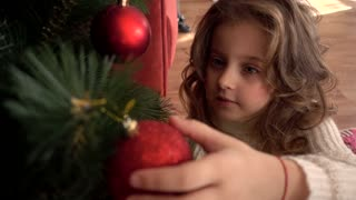 Little Girl admires a red glass ball on Christmas Tree