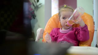 Little girl drinks juice from a bottle with a nipple