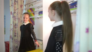 little girl model looks to the mirror - fashion dress