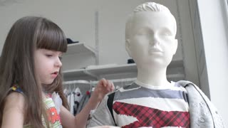 Little girl plays with a boy mannequin in a clothing store