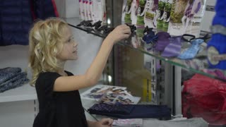 Little Girl Shopping For Clothes In Clothing Store