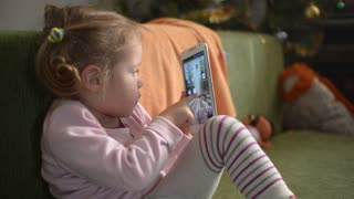 Little Girl touching A Screen Of Mobile Phone sitting On A Sofa