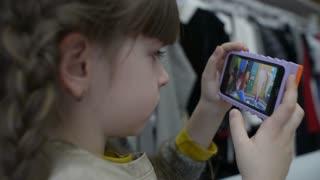 Little girl watching a cartoon on the phone
