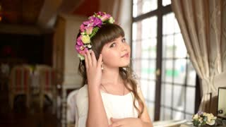 Little girl with a wreath of flowers in hair dye before the mirror
