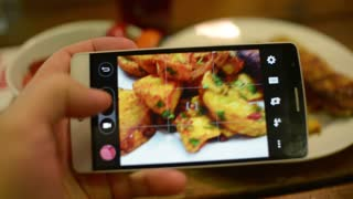 Make Photo Of Food In A Restaurant With Mobile Phone Camera For Social Network