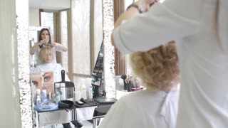 Make up artist and hair dresser work with beautiful blonde woman model