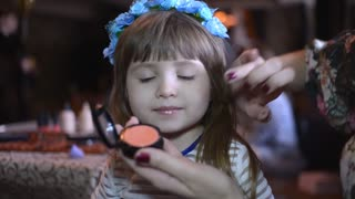 Make-up artist does the skin tone of a little girl model
