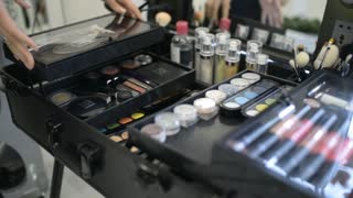 Make-up artist opens a large case with cosmetics palette