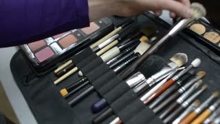 Make-up artist takes a brush and choose a color from a palette of shadows
