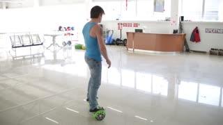 Man acrobat balancing Segway motorized scooter io hawk - shows tricks