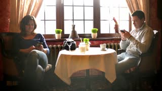 Man and Woman Couple at the restaurant against window with Mobile Cell Phones in Hands