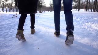 Man and Woman walking on snow in winter park taking hands romantic day