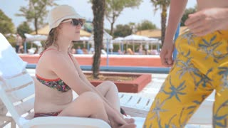 Man and young sexy girl talking on a lounger near pool