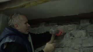 Man breaks parses Brick Wall with Chisel and Hammer