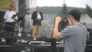 Man cameraman adjusts the camera on the crane