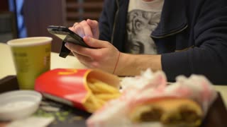Man chating sms by Mobile Sell Phone at the Table fast food cafe McDonald's